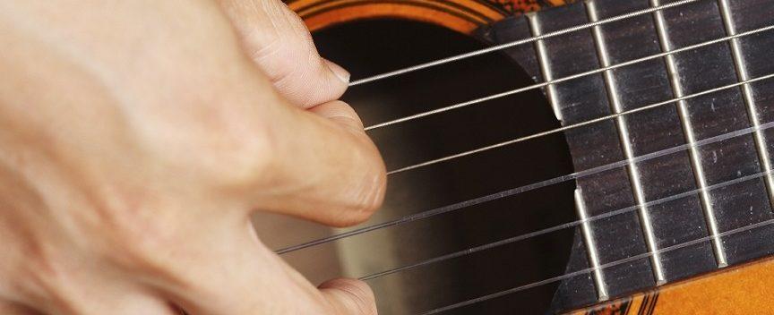 Image of hand strumming guitar strings