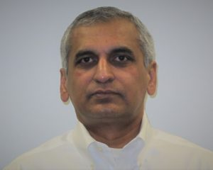 Prasad has gray hair and is wearing a white shirt.