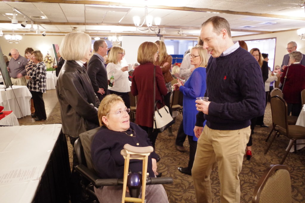 A female and male guest talking. The female guest is seated in a wheelchair with crutches wearing a black sweater, the male guest is standing wearing a blue sweater.