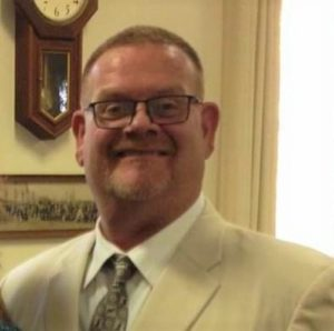 Mark is wearing a dress shirt, tie, and formal jacket. He has a buzzed head and goatee with glasses.