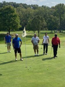 Five men standing on golf course at Weaver Ridge Golf Club.